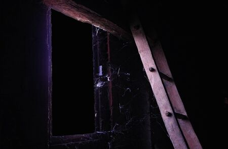 Window and ladder of spooky attic with a lot of dust and cobweb. Stock Photo
