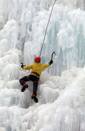 edge of the ice: Ice climber on steep frozen waterfall