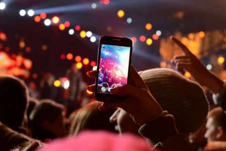 holding back: People holding their smartphones and photographing concert Stock Photo