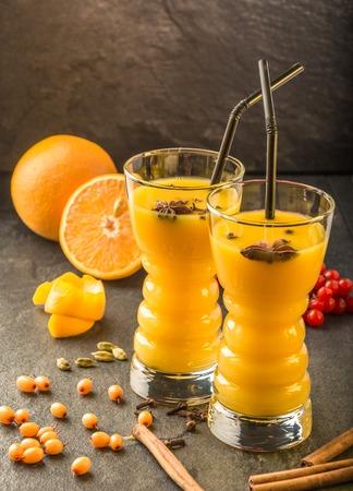 orange sea buckthorn juice with orange, sea buckthorn , cinnamon, carnation, cardamon and viburnum on a dark table