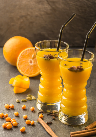 orange sea buckthorn juice with orange, sea buckthorn , cinnamon, carnation and cardamon  on a dark table
