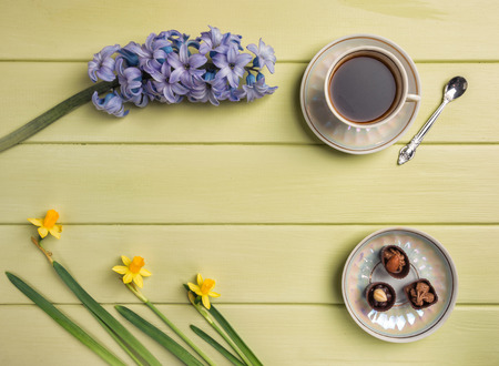 Cup of black coffee,  and flowers on a wooden background. Top view. Copy space