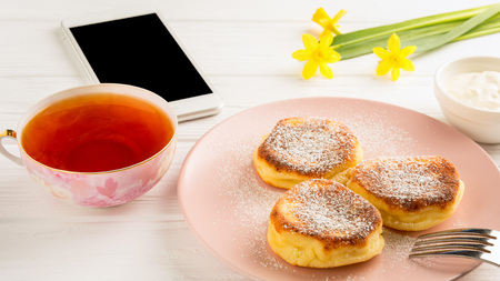 Cheese pancake with powdered sugar, black tea, flowers and smartphone on a white wooden table.