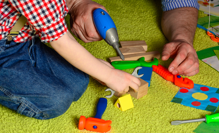 teaches: the father teaches the child to use the tool
