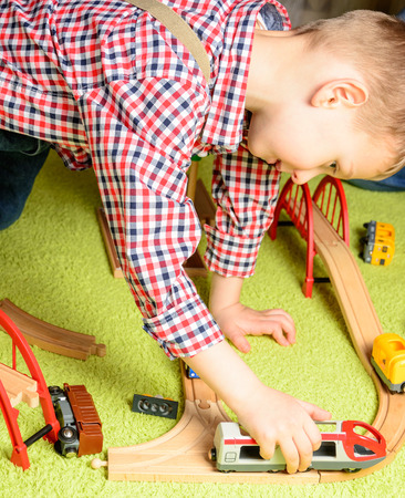 the boy plays the wooden railway sitting on a green carpet