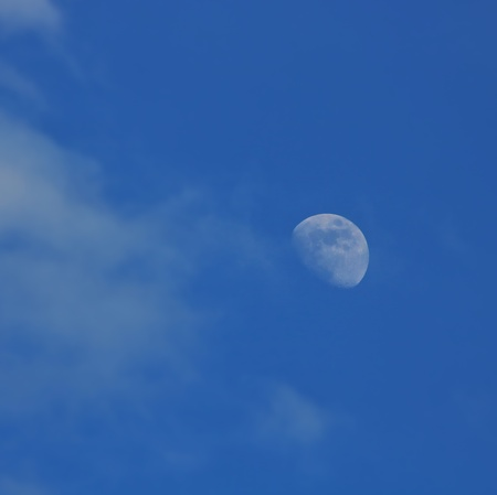The moon in the afternoon on a blue sky, clouds Stock Photo