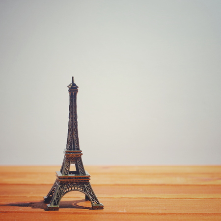 Eiffel Tower metall figure in the background of an old wooden texture table. empty copy space for inscription or other objects Stock Photo