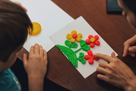 clay therapy. plasticine therapy. a boy sculpt clay figures. the teacher help him. Banco de Imagens
