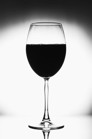 Glass for wine black and white photo with black vignette. A tall glass with a thin stem. The wine glass is half full, the background is blurred and elegant.