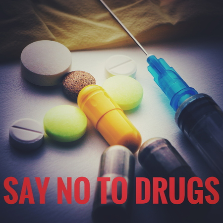 Man from the pills lies next to the syringe. Say No To Drugs concept. Banque d'images