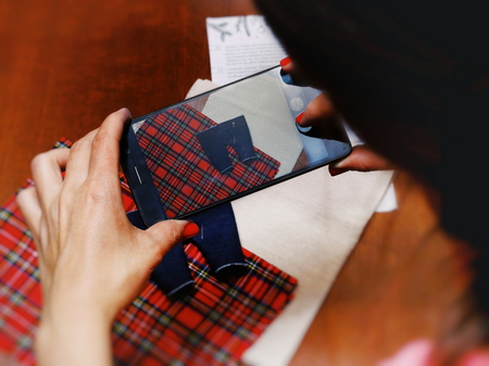 Woman Photographs on Smartphone sewn clothes for Dolls. Home business concept.