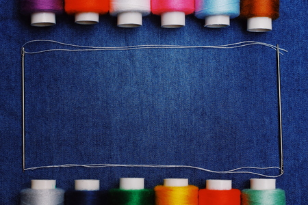 Background jeans fabric, thread, needles with threads, colorful background.