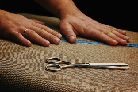 Men Hands Cut Fabric on a dark background. Scissors in male hands. Tape measure. Measure the fabric.