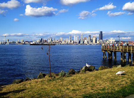 Scenic View of Seattle Skyline from Alki park near a seafood joint. There is the Seattle Space Needle, and people fishing off the pier as well.