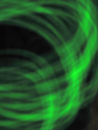 Green Swirl Background abstract representation of green coils on a black background.