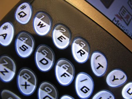 backlit keyboard: Text Messaging is a close-up shot of a PDA mobile internet communications device with backlit characters with a QWERTY keyboard. Stock Photo