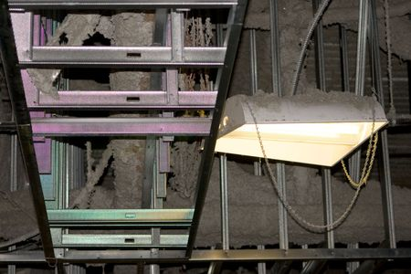 rafters: Industrial Rafters Construction Dust is a capture of an exposed area. There is a mix of insulation and dust visible next to a light that is creating a rainbow effect on the structure that looks like a ladder. Stock Photo