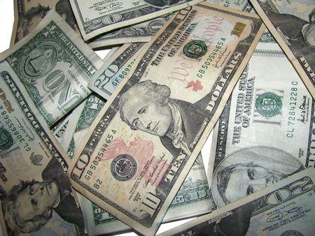 moola: Pile of US Dollars on White. Focus is on the ten dollar bill.