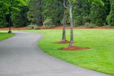 Weg in het Park heeft groen gras en bomen met houtsnippers in dit landschap prachtig gemanicuurde park. Stockfoto