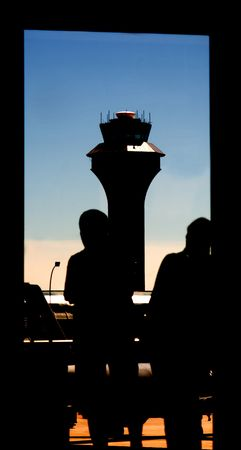 Silhouette of Airport Tower and Passengers Waiting captured in this uniquely framed picturesque of the aviation transportation industry.