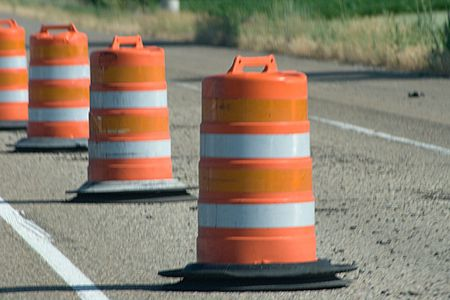Orange Construction Warning Barrels is a row of barrel cones that are bright orange on the highway.