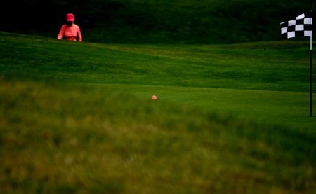 Pink Golf Lady Abstract with ball and Checkered Flag with her ball having just landed on the green during a night session of golf.  Stock Photo