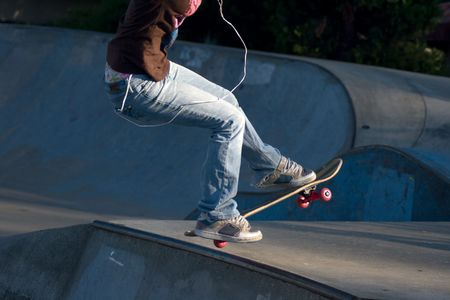 Young Girl on Skateboard jumping with MP3 Player to the top of the rim of a skate park pit. Stock Photo