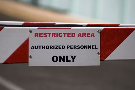 Restricted Area Sign Authorized Personnel Only barricade at this automobile entrance.