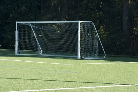 Soccer Goal on Artificial Turf field set both in the sun and shadows. Stock Photo