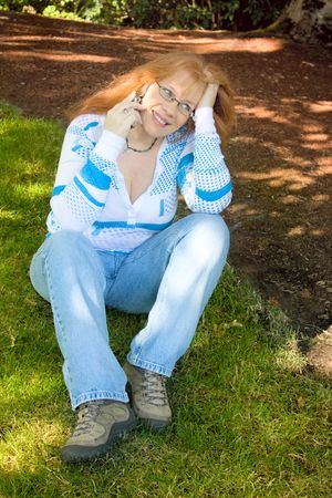 Beautiful Redhead Woman day dreaming and talking on Cell Phone sitting on green grass under the shadows of a tree. She's wearing blue jeans and is wearing glasses and a necklace. Stock Photo - 5282730