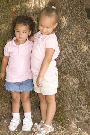 Two Young Ethnic Sisters with Questioning and Mischievous looks on their faces. They have their arms around each other as hold each other while standing against the trunk of a large tree.