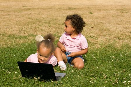 Two Beautiful Ethnic Girls with Laptop Computer in the park on a field of clovers and brown and green grass.