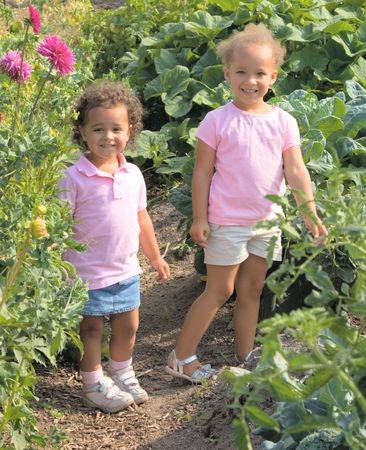 Two beautiful ethnic sisters Little girls in the garden are wearing pink shirts and have adorable smiles.