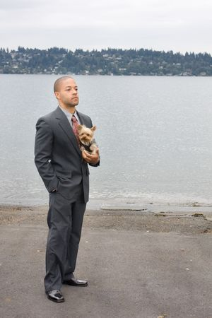 be dressed in: Ethnic Business Man and Yorkshire Terrier Dog are standing next to the lake. He is dressed in a suit and tie and seems to be contemplating something.