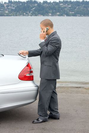 Ethnic Business Man Making a Sale on Cell Phone holding a calculator while standing by his luxury car at the lake.  Stock Photo