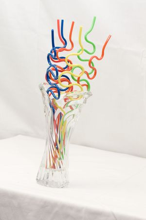 wacky: Wacky Wavy Curvy Straws in Glass Vase on a white table against a white background. Stock Photo