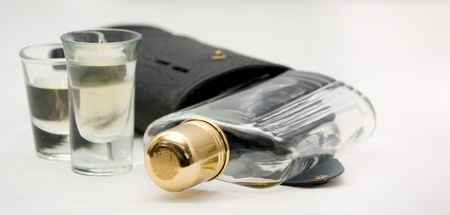 Shot Glasses with Whiskey Alcohol flask and case on a white background. The flask has a brass cap.