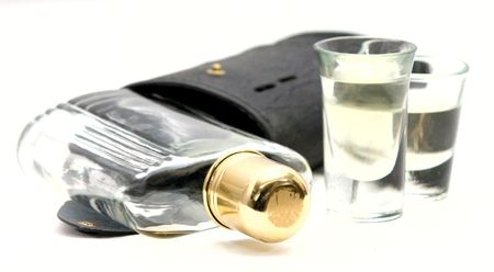 Shot Glasses with Whiskey Alcohol flask and case on a white background. The flask has a brass cap.  Stock Photo - 5498190