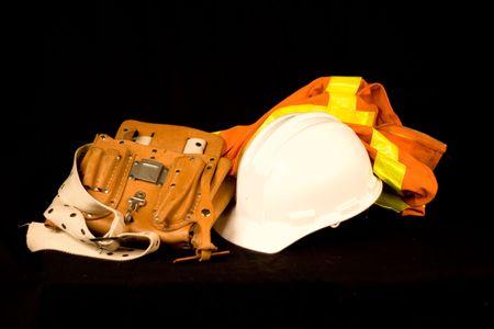 Tool Belt Bouw Hard Hat Reflective Safety Vest geïsoleerd op een zwarte achtergrond. Stockfoto