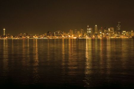 Seattle Skyline with Space Needle with Night Lights across the waters of the Puget Sound. The buildings and waters are lit up in the skyscrapers on this picturesque background. Stock Photo