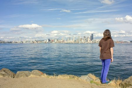 puget: Seattle Space Needle and Skyline with Young Girl Looking across the Puget Sound from Alki.