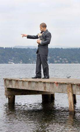 Ethnic Business Man Pointing and Yorkshire Terrier Dog standing on a pier next to the lake. Stock Photo - 5525453