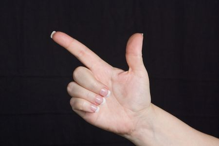 Female Hand Pointing with French Manicure Nails isolated against a black background.