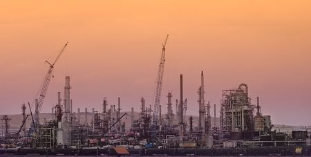 Building Oil or Natural Gas Refinery with Construction Cranes against an orange sunset background. Stock Photo - 5785555