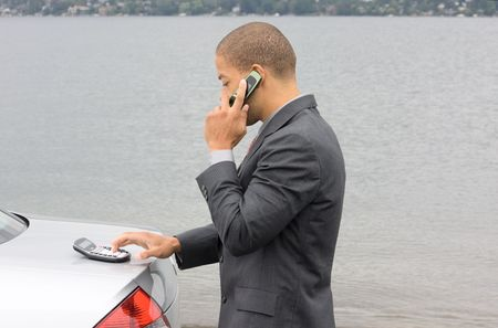Ethnic Business Man using calculator while talking on cell phone. He is parked at the shore of the lake. Reklamní fotografie