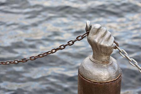 Mano de acero sosteniendo la cadena contra el agua de un lago o el Oc�ano