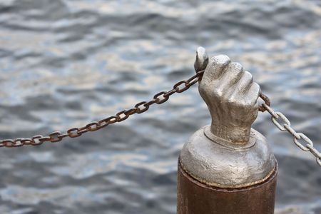 Steel hand holding chain against the water of a lake or ocean