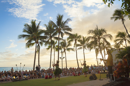 hawaii oahu waikiki beach june 2012: a small orchestra plays the typical hawaiian music while dancers dance the hula at sunset Editorial