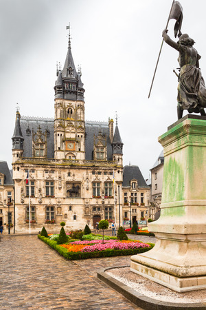 ville: Compiegne September 2012 - In September tourists visit this historic square to admire the Jeanne Darc statue and the old hotel located in front of it.