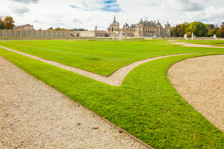 chantilly: Chantilly September 2012 - In September, the tourists visit the Anglo-Chinese garden in Chantilly Castle to walk  in nature and admire the well kept grass. Panoramic view of the Castle from the garden.